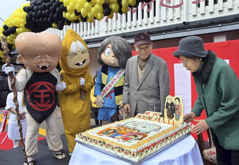 Shigeru Mizuki and his wife blow out the candles on his 90th birthday cake